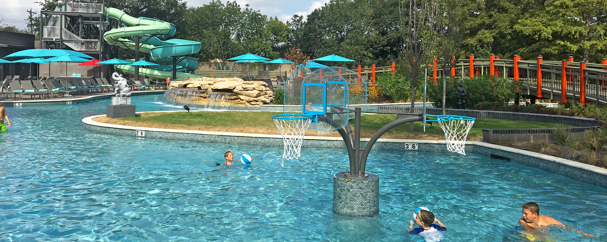 Kids playing at a basketball hoop in a pool