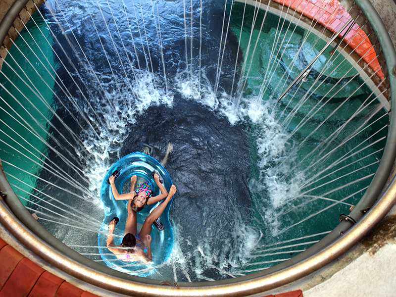 Overhead view of people floating under a hole with water coming out of it
