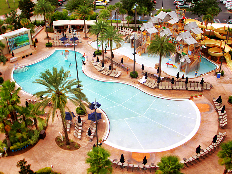 Aerial view of a pool with palm trees and people around it at Gaylord Palms