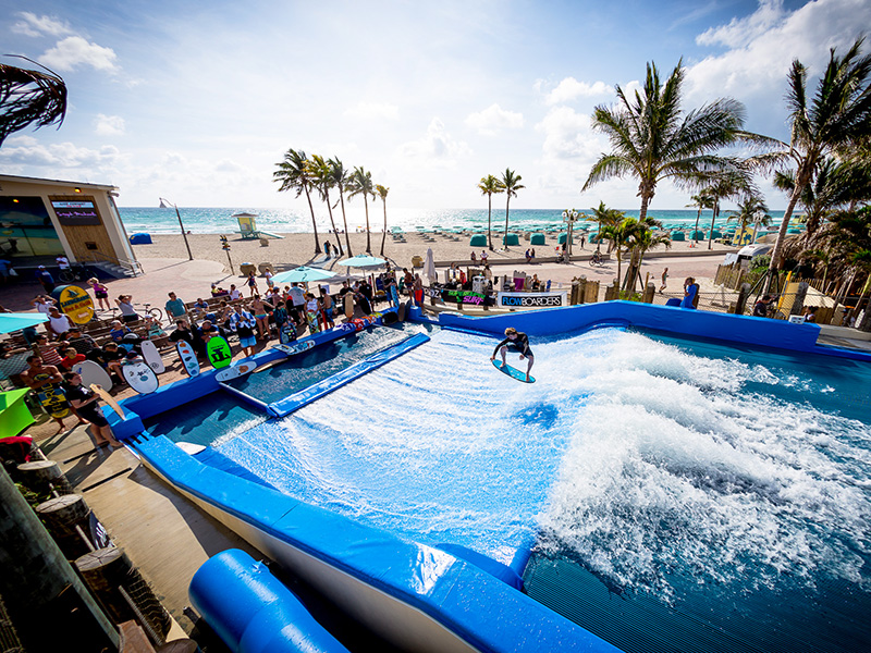 Person surfing on the flowrider with a crowd watching and the ocean in the background.