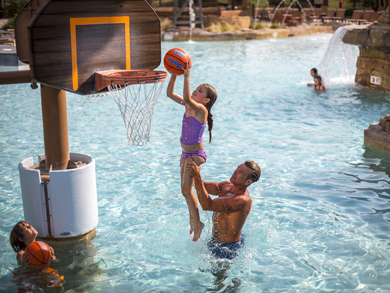 A man lifting a young girl up to a basketball hoop in the water