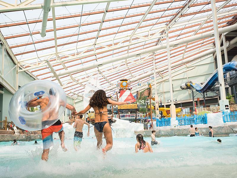people running into the wavepool at aquatopia indoor waterpark underneath the texlon roof