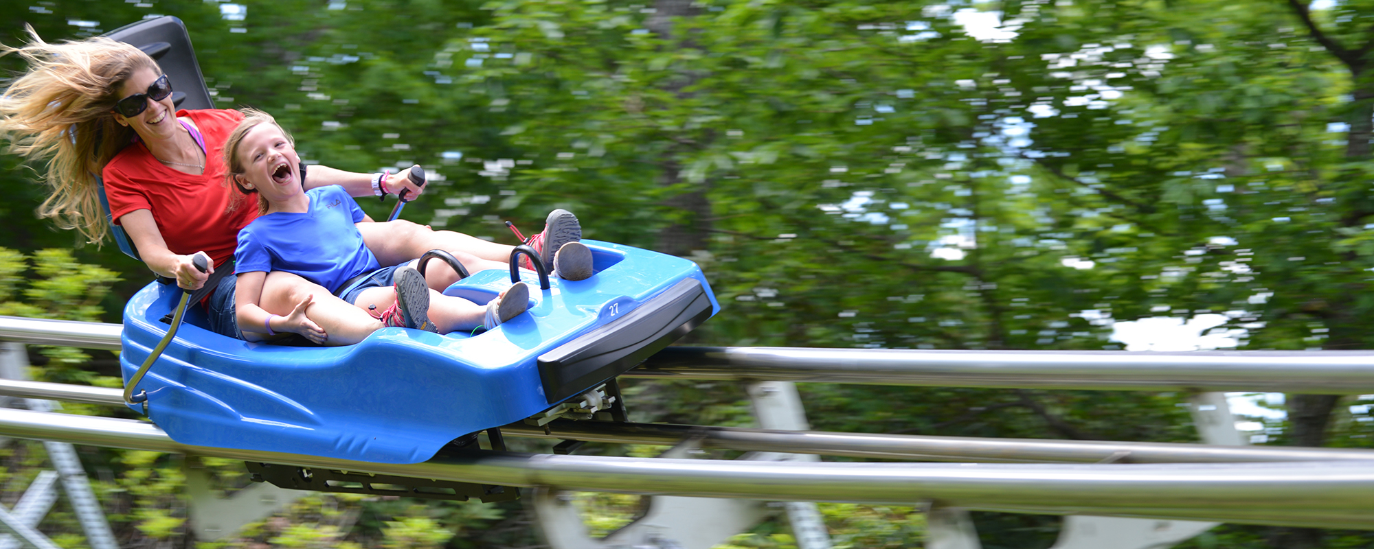 Woman and child riding down the mountain coaster
