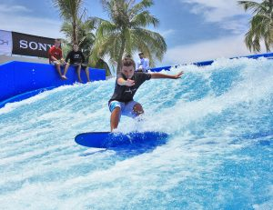 Boy riding FlowRider surf simulator