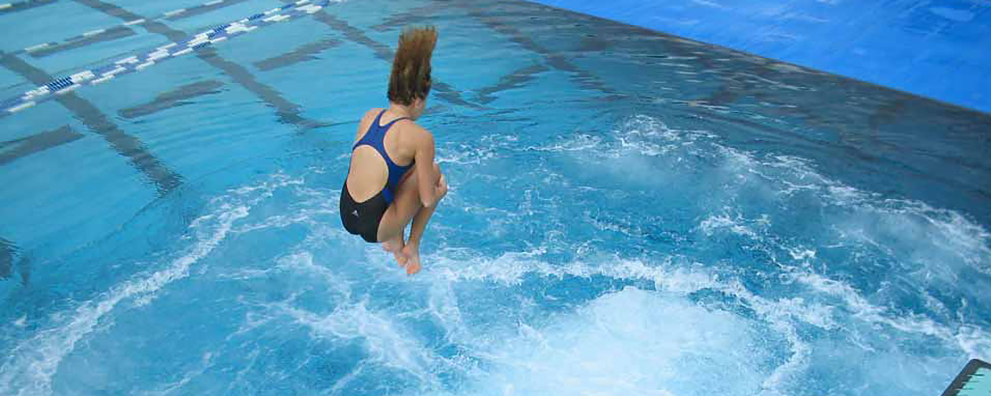 A girl doing a cannonball into a pool with sparger systems running