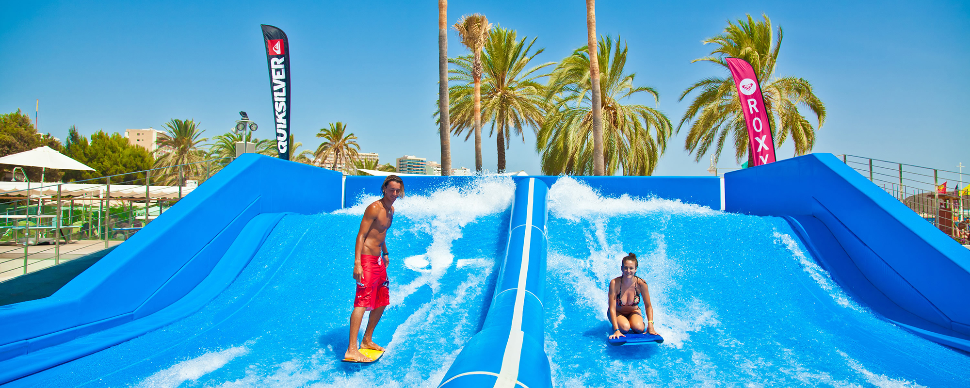 A guy standing and a girl kneeling on the flowrider double