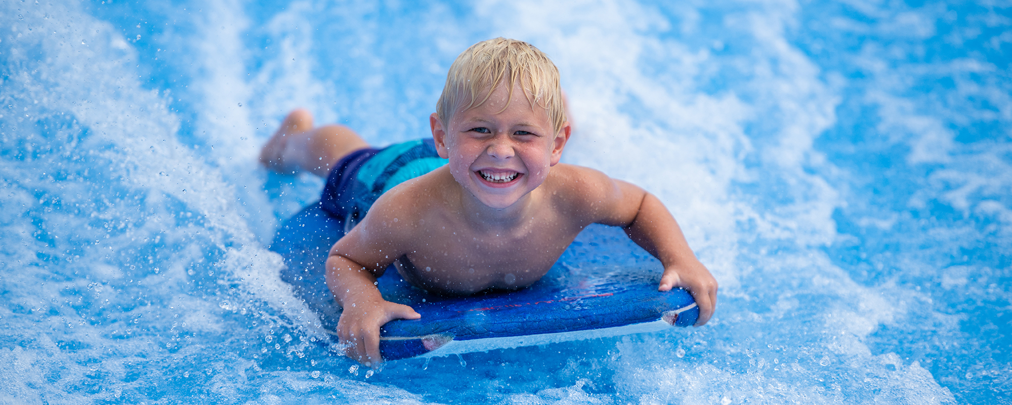 Young boy riding on the flowrider
