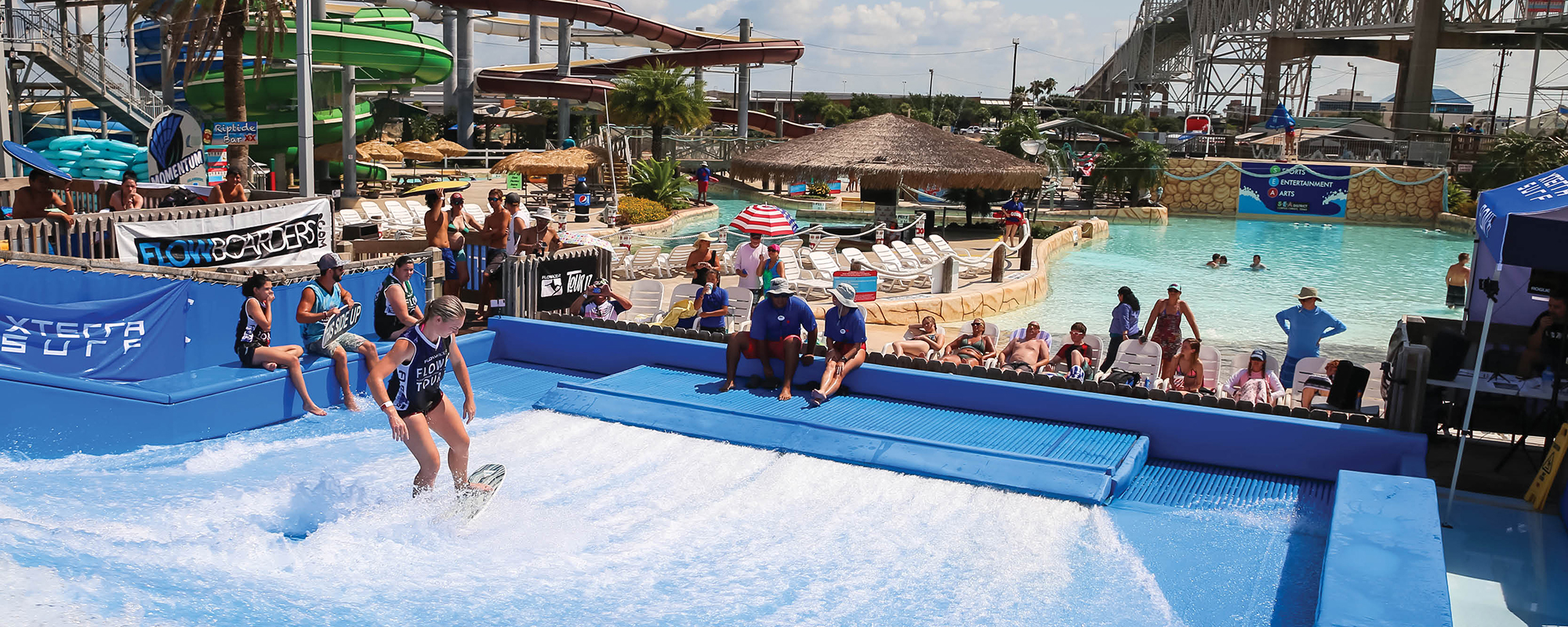 Girl surfing on the flowrider with people watching around it and slides and a pool in a background