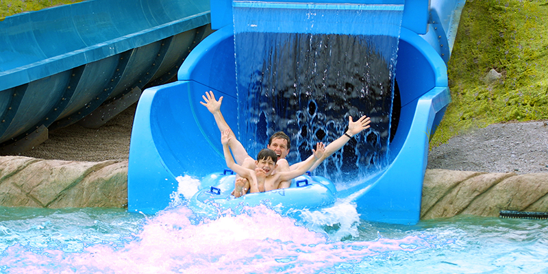 A Father and Son Are Exiting a Water Slide on a Double Tube