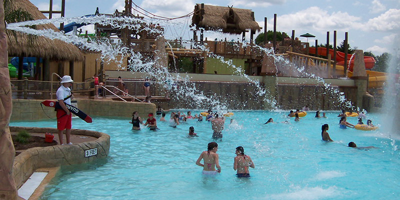 Families and Friends Having Fun in the Wave Pool with Spray Features