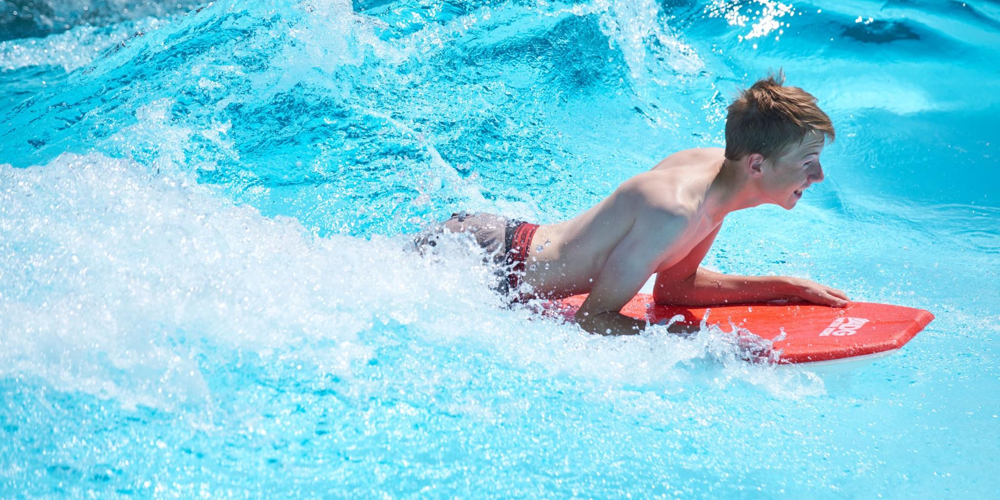 Boy on a boogie board in a wave pool