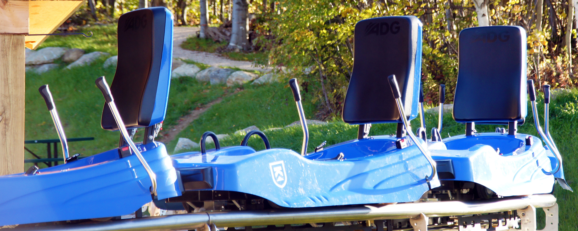 Three blue mountain coaster carts side by side.