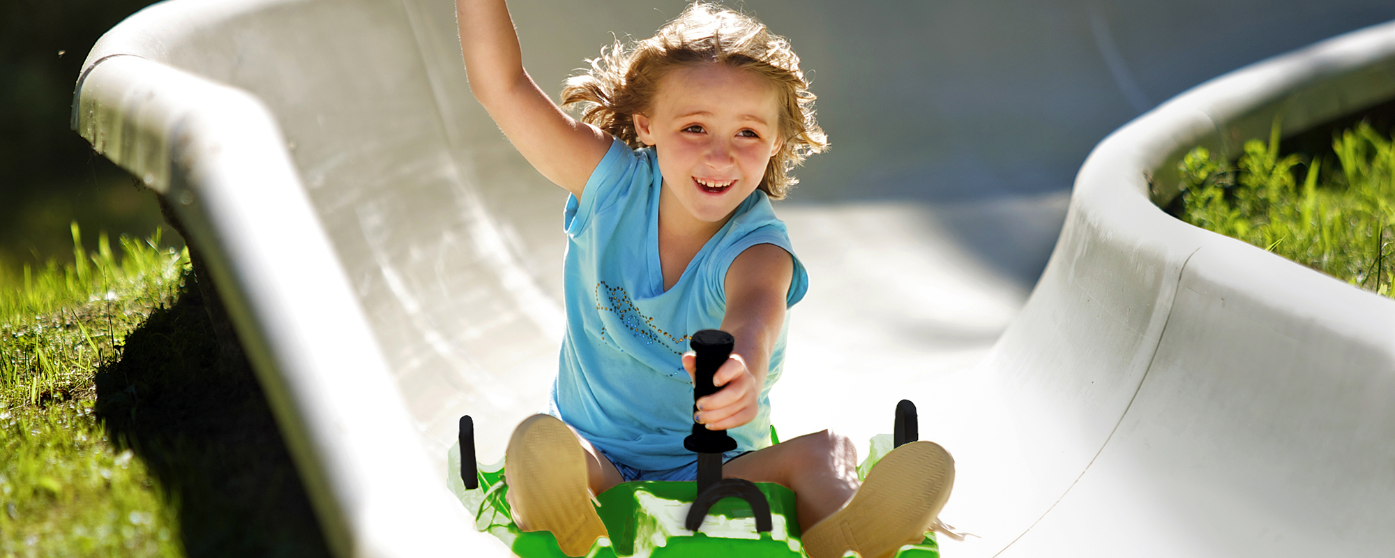 A young girl riding down the alpine slide with her arm up