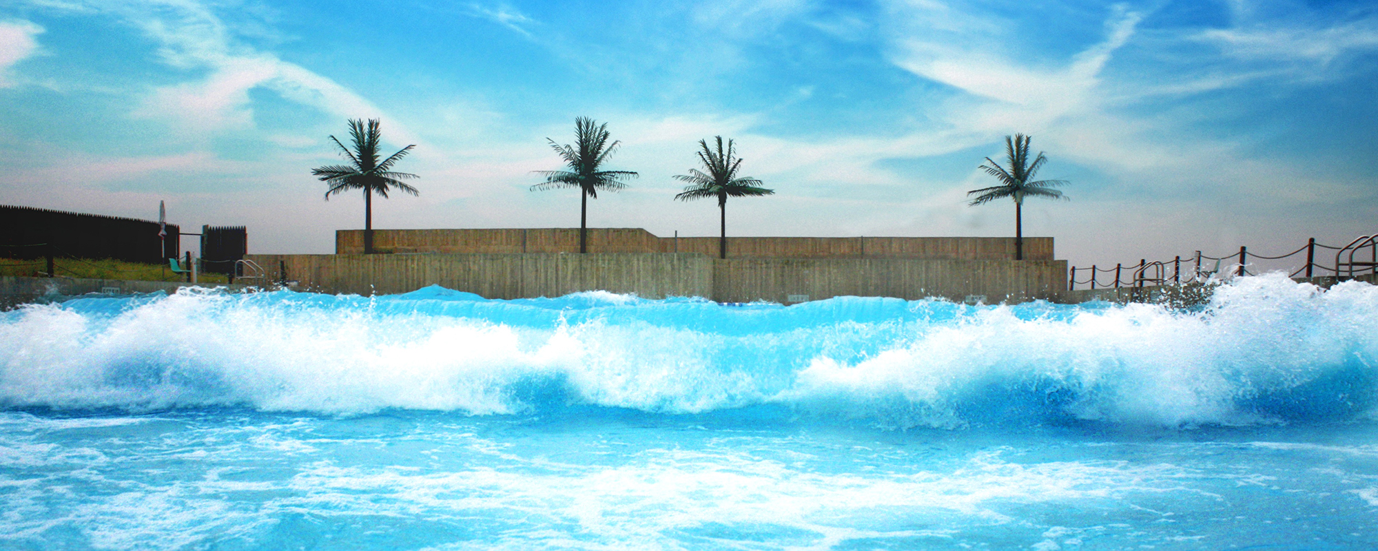 A wavepool with four palm trees behind it