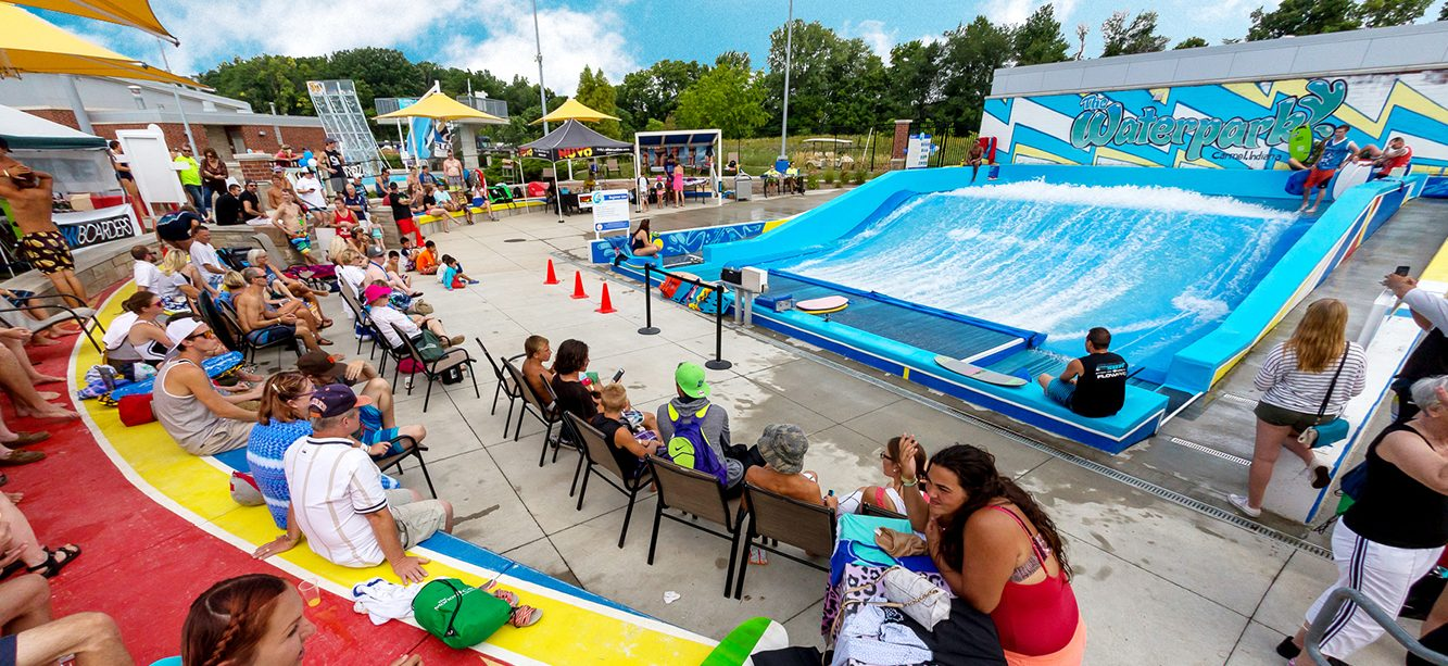 People watching surfers on a flowrider surf machine