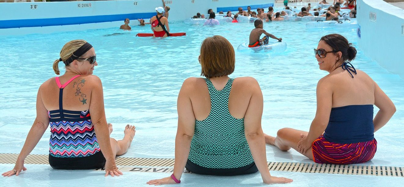 Women sitting by the edge of a wave pool at a municipal water park