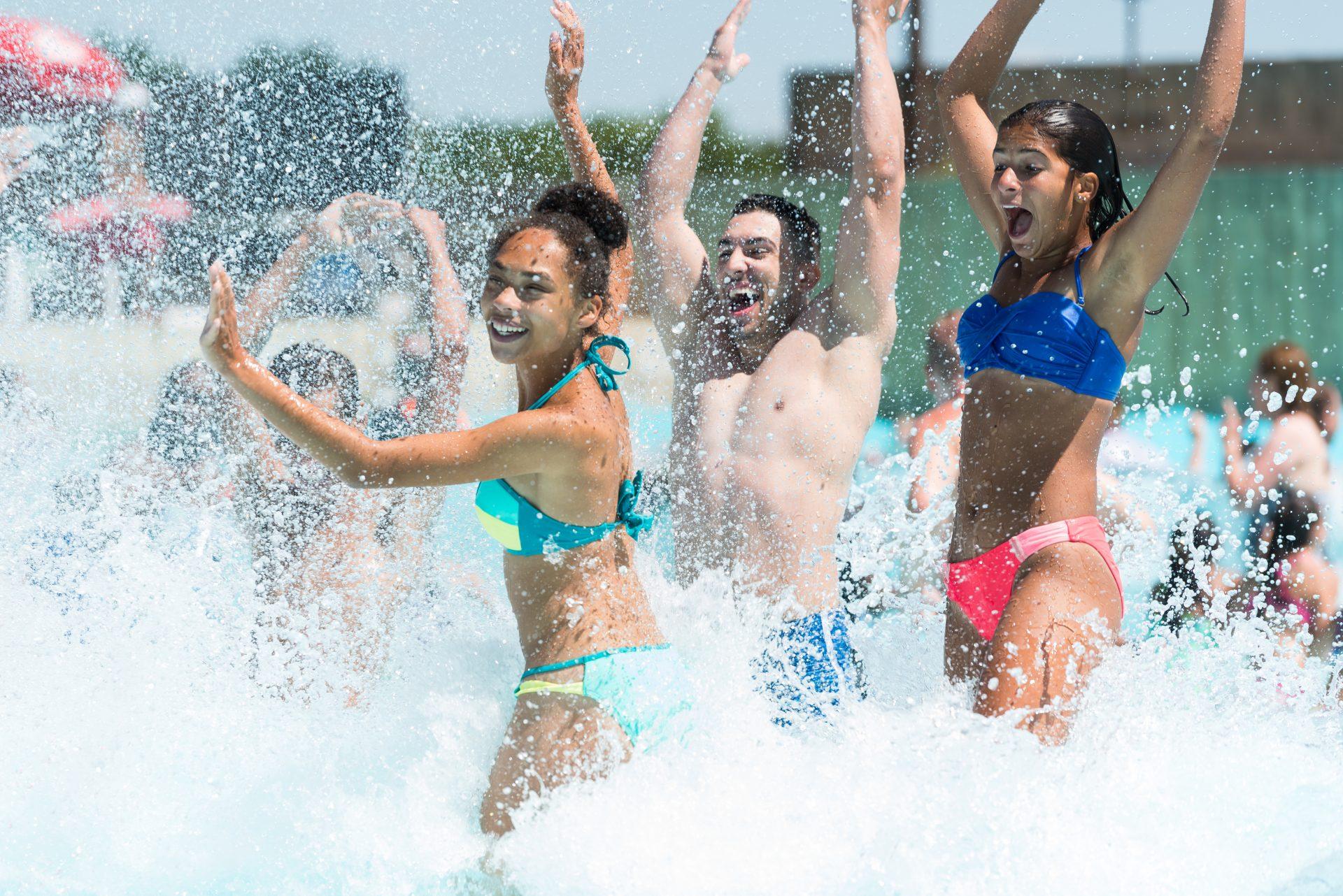 teens splashing in water park wave pool attraction