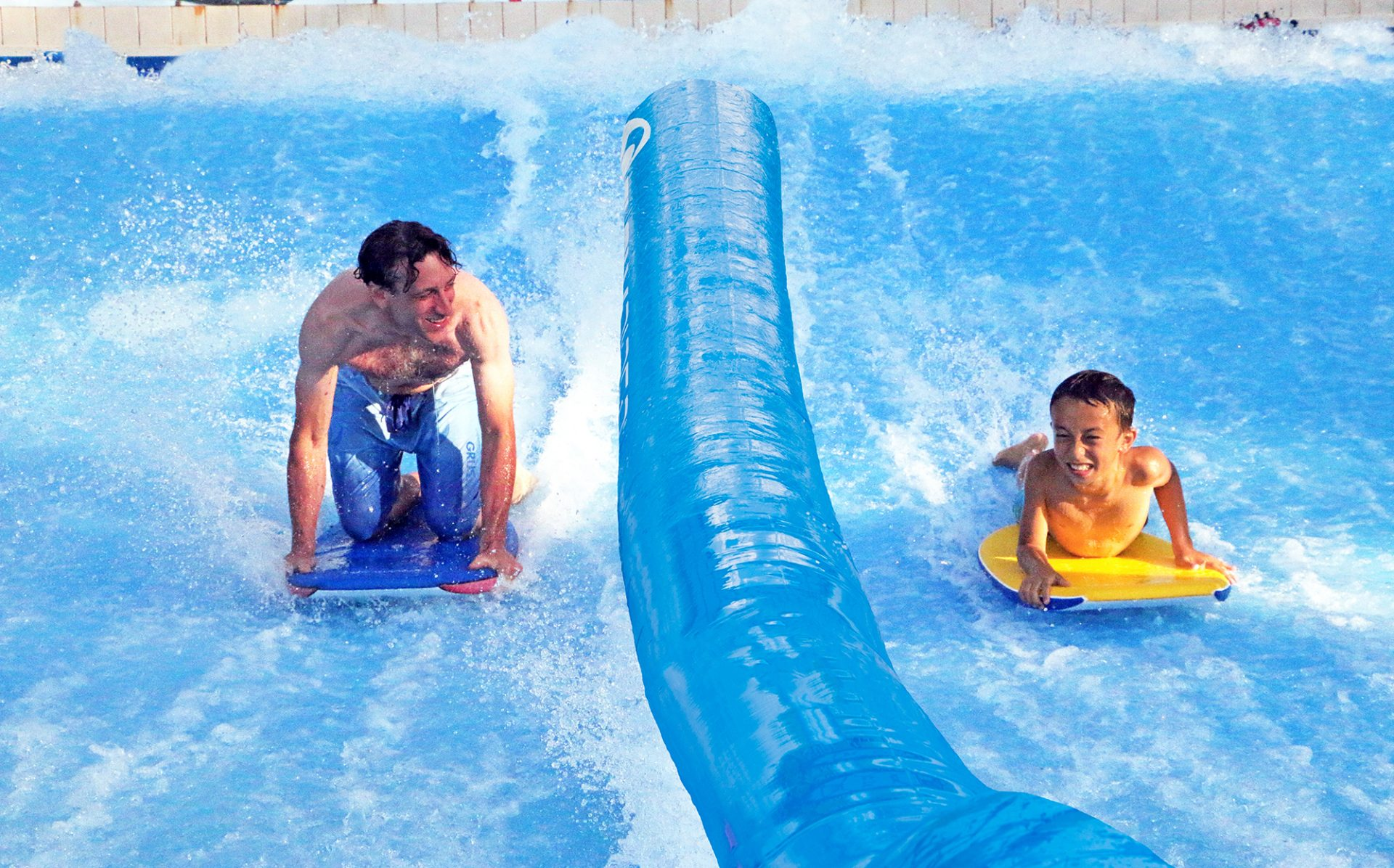 father and son riding on flowrider surf ride